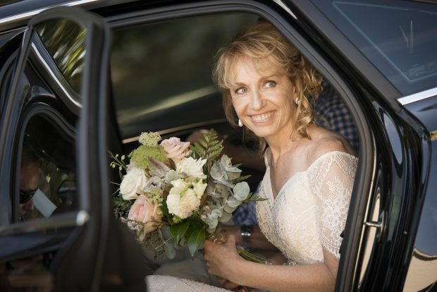 Woman wearing a wedding dress & smiling while seated in a bridal car holding a bouquet of flowers