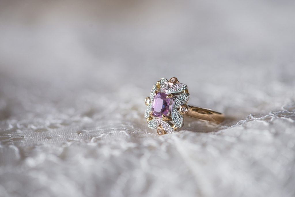 Engagement ring with purple stone lying on wedding dress fabric