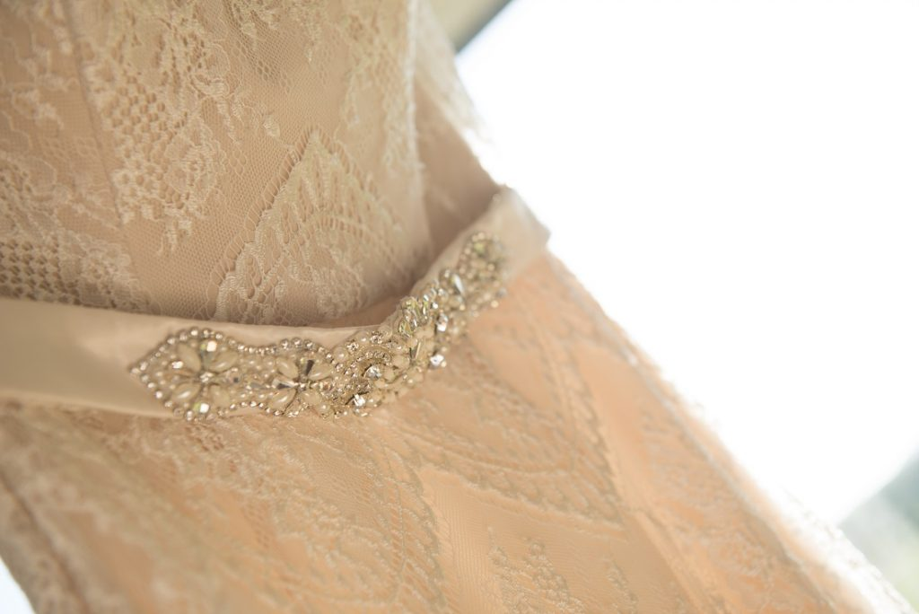Close up mid section of a wedding dress wth lace overlap featuring a beaded belt