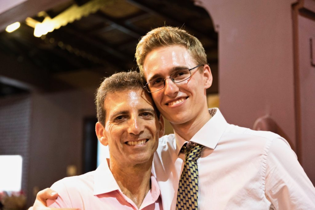 Upper body shot of 2 men standing side by side with arms around each other smiling